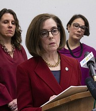 Gov. Kate Brown issues an order during a press conference with state and local government officials Thursday in Portland to close all schools in the state because of the coronavirus epidemic. On Monday, she went further to limit crowds of 25 people and ordered restaurants and bars to either shut down or serve take-out only. (AP photo)