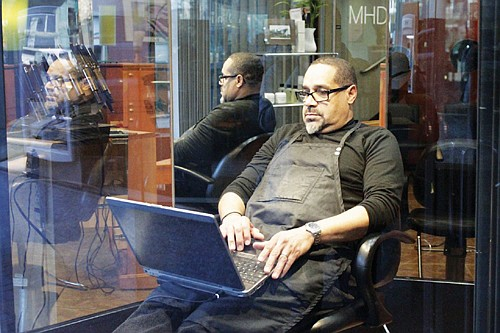 Anthony Crowell sits at his barber station, downtown, after multiple customers canceled haircuts Monday because of fears about the spread of the coronavirus. Crowell usually has a steady clientele of business people at his barber shop but customers have stopped coming in recent days. (AP photo)