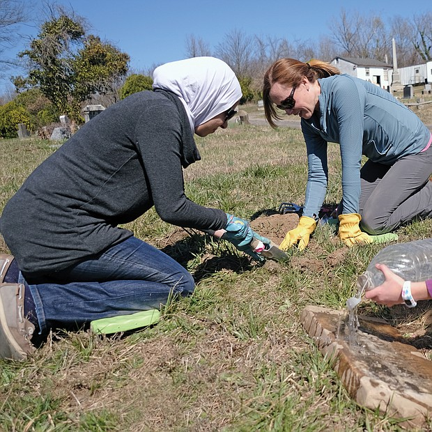 "Tessneem Khalil, 7, right, helps uncover gravestones in the 104-year-old Woodland Cemetery in Henrico County. She is working with her mother, left, Rania Fetouh, and Kathleen Harrell, her teacher at Shady Grove Elementary School in Henrico County. Ms. Harrell has volunteered consistently on Sunday afternoons with Dr. John W.J. ""Bill"" Slavin to improve the neglected burial ground best known as the last resting place of Arthur Ashe Jr., the Richmond native who earned international renown in tennis and as a humanitarian."