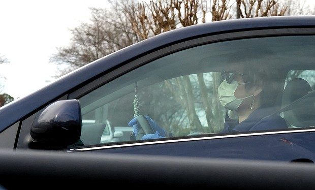 A motorist in Western Henrico wears a protective mask and gloves on Saturday.