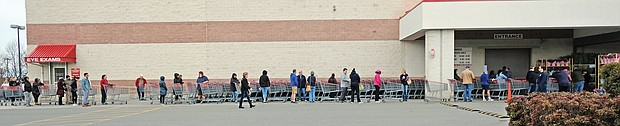 Shoppers practicing social distancing while waiting for Costco on Broad Street in Western Henrico to open last Saturday.