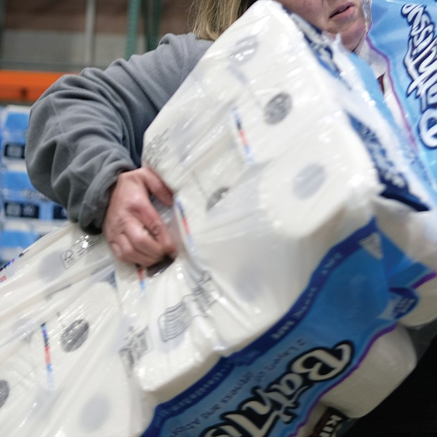 A customer stocks up on toilet paper at Costco, while below, others wait their turn at the Costco Saturday.