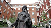 A Jesuit statue stands in front of Freedom Hall at Georgetown University in Washington. Students at the private university voted last year to add a fee to tuition to help pay for projects in communities that are home to descendants of the 272 slaves who were sold in 1838 by the university to help pay off the school's debts.