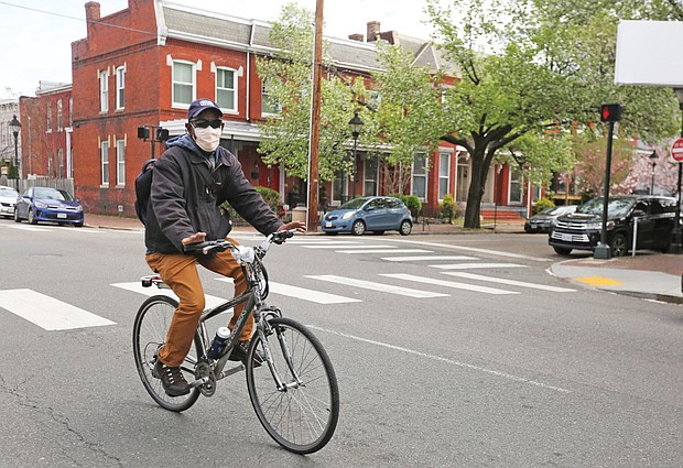 A man rides his bicycle through Jackson Ward on Tuesday wearing a medical mask as an extra precaution during the continuing spread of COVID-19 in Virginia.