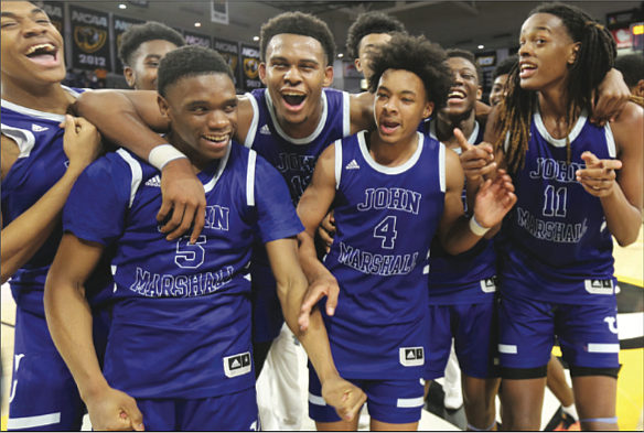 The John Marshall High School basketball team celebrates after defeating Gate City High School 75-57 to clinch the state 2A crown on March 12 at the Siegel Center in Richmond.