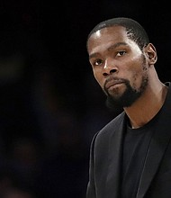 Brooklyn Nets' Kevin Durant watches the team's NBA basketball game against the Los Angeles Lakers in Los Angeles. Durant is among the four Brooklyn Nets who have tested positive for the new coronavirus.  (AP photo)