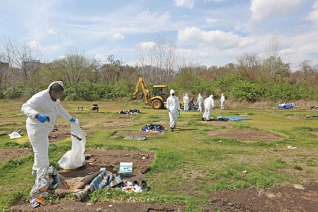 City employees dressed in hazmat suits Friday to clean up Cathy's Camp on Oliver Hill Way. The property that belongs to Virginia Commonwealth University is to be fenced off to prevent a return of a homeless encampment.