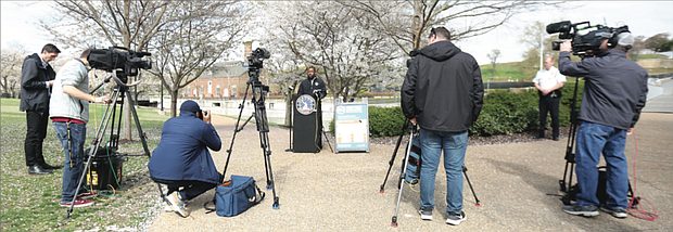 Reporters listen as Mayor Levar M. Stoney warns people on Tuesday that the city will shut down parks and other outdoor spaces if people don't stop gathering in groups to play basketball and other games or continue to congregate at the river.