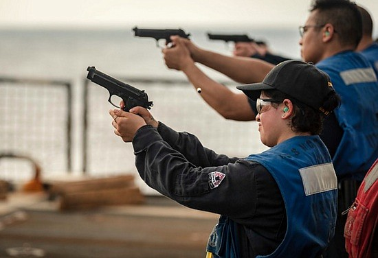U.S. Navy Boatswain's Mate 3rd Class Victoria Torres, from Houston, fires an M9 pistol during a handgun qualifications course on ...