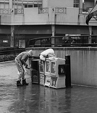"If you look very closely at this photograph you will notice the man is reaching into a Baltimore Times newspaper street bin.  ""My purpose for this image is to show humanity during covid-19. This image shows a man using a Baltimore Times newspaper street box to keep his belongings dry""  - Kyle Pompey"