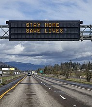 A reader board over Interstate 5 northbound south of Eugene, Ore. encourages motorists to stay at home due to coronavirus. (AP photo)