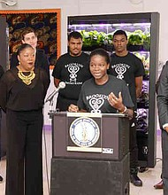 Dez-Ann Romain is pictured to the left of the girl speaking.