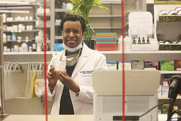 Dr. Shantelle L. Brown, the pharmacist, owner and operator of HOPE Pharmacy inside The Market@25th, is making hand sanitizer to ...
