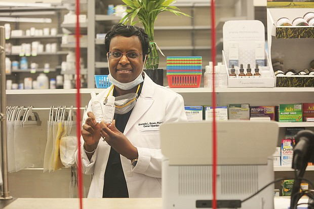 Dr. Shantelle L. Brown, owner of HOPE Pharmacy, shows the hand sanitizer the pharmacy is producing for free distribution to first responders. The sanitizer also is for sale to the public at the Church Hill pharmacy.