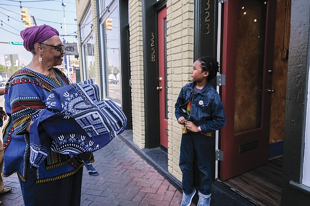 Ms. Shakoor gives 7-year-old Mansa Makamu, son of fellow 2nd Street merchant Ife Robinson, a dashiki from her store. It's all a part of the connection.
