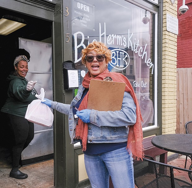 Mikki Robinson at Big Herm's hands a to-go order to Shonda Harris-Muhammed.