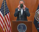 Gov. Ralph S. Northam puts on a mask during a media briefing on Monday that was made by inmates in the state Department of Corrections. The demonstration was to remind Virginians to cover their noses and mouths when they go out in public to help stop the spread of COVID-19.