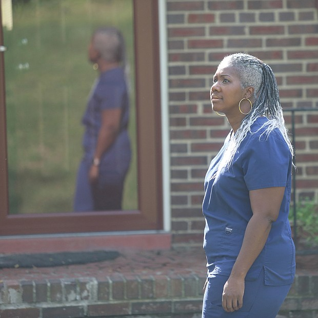 """Cheri Gupton, stands outside her home in Chamberlayne Farms before heading to work as an acute care nurse for DaVita Dialysis servicing various hospitals in the area. She has been working as a nurse for 11 years. She says she doesn't know which hospital she will be assigned to from day to day, but she has no doubt that she is needed. Most of her patients, she says, tested positive for COVID-19. Her silver lining? """"Due to the somber reality that we may not always have our loved ones around, I find myself more intentional with calling them and letting them know how much I love them or just asking how they are doing."""""""
