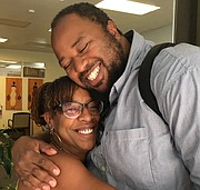 Felicia Wells-Thomas of the small businesses micro lender Micro Enterprises Services of Oregon (MESO) gets a big hug from Ime Etuk, a videographer and one of her clients who obtained services from the nonprofit.