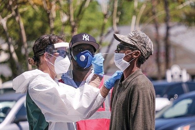 Lamire Balde is tested for the coronavirus by health care professionals at a Richmond Health District walk-up testing event Wednesday at the Southwood Apartments in South Side.