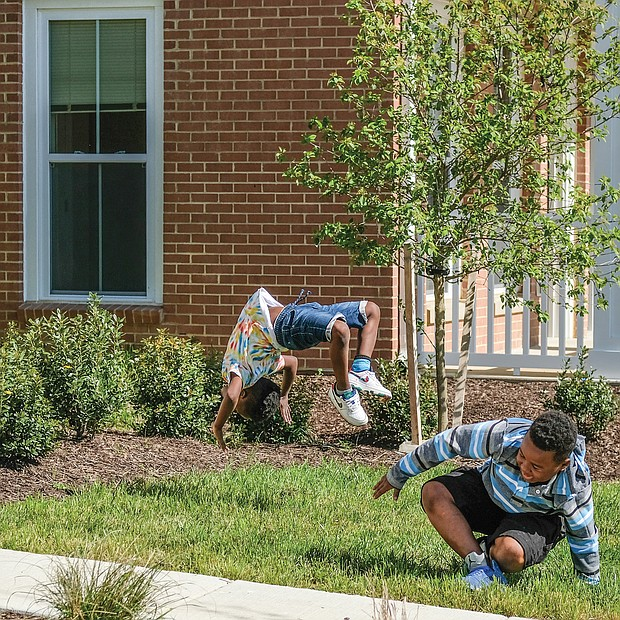 Montrell Mosley, 6, left, keeps the backflip and cartwheel party going as Demario Otey, 9, and Aiden Otey, 5, finish their rotations last Saturday in the 1700 block of Armstrong Way in Church Hill North.