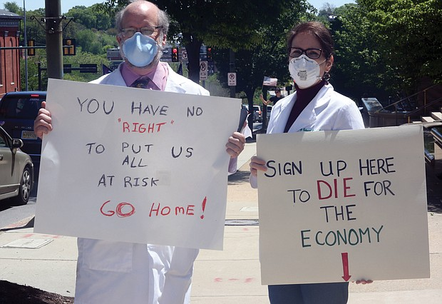 Dr. Erich Bruhn, a general surgeon from Winchester, and his wife, Kristin Bruhn, a nurse who works in her husband's practice, wear masks as they walk among protesters on Broad Street in Downtown with their own message of safety against the virus.