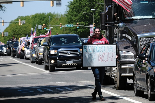 A woman walks with her sign as traffic on Broad Street comes to a standstill.