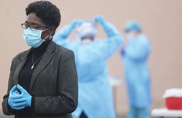 City Council President Cynthia I. Newbille listens intently during a news conference Tuesday before the opening of an outdoor COVID-19 testing site near Creighton Court in the East End. Behind her, medical personnel from the Richmond City Health District suit up to administer the tests.