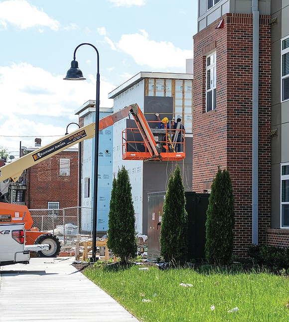 Workmen use a bucket truck to install panels at the 154-unit Jackson Ward Apartments in the block bounded by Duval, ...