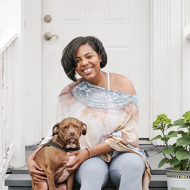 "Ashley Williams, with her dog, Sebastian, a pit bull-spaniel mix, on the front porch of her East End home, is happy to stay in during the COVID-19 pandemic. Her family, she says, has experienced health scares in recent weeks, both related and unrelated to the coronavirus. ""I have always valued family and friends, yet the communication with loved ones is even more cherished than before,"" said the founder of BareSOUL Yoga. The experience also has shifted how she connects with people and the community — through online offerings and resources. The silver lining? ""I am able to appreciate, explore and enjoy my home."""