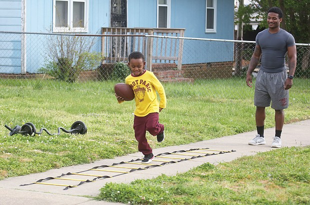 Virginia Union University running back, Andre Mack, 23, works out with his 5-year-old nephew, Ka'Reem Moore, on Tuesday in the 700 block of 30th Street in Church Hill. The youngster wants to play football like his uncle, a junior at VUU. The coaching and workout sessions also keep Mr. Mack in shape until the Panthers practice again in August, according to Mr. Mack. Until then, Mr. Mack is finishing his college courses online and having Zoom meetings with his teammates.