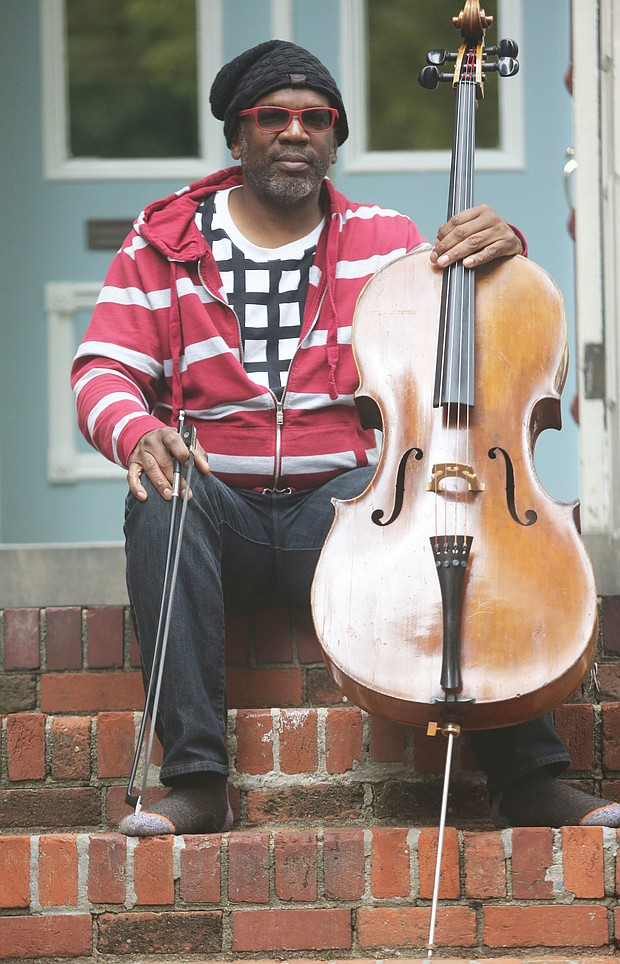"""Paul Rucker, a visual artist, musician and composer, sits with his cello on the steps of his home in Downtown. He is an iCubed Arts Research Fellow at Virginia Commonwealth University. The pandemic, he said, """"offers those, especially with privilege, a time for reflection. I think this is an opportunity to evaluate and move in new directions. This is not a time for fear."""""""