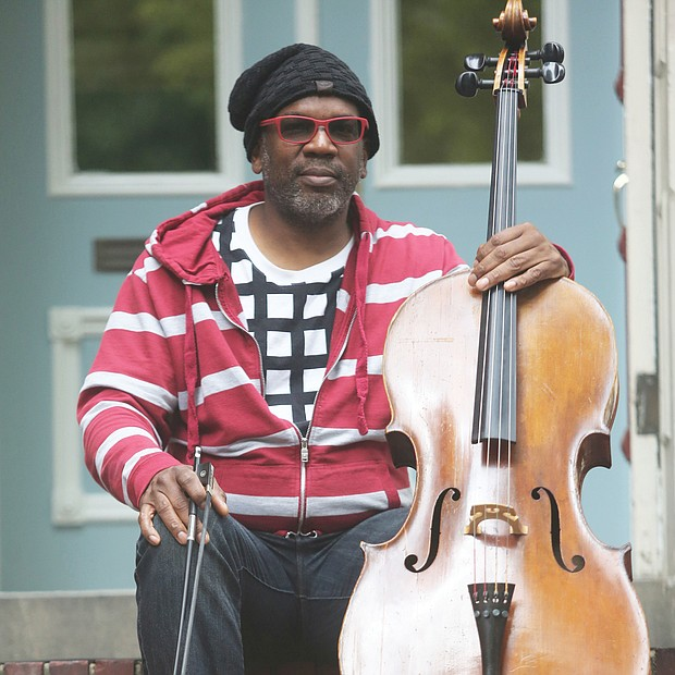 "Paul Rucker, a visual artist, musician and composer, sits with his cello on the steps of his home in Downtown. He is an iCubed Arts Research Fellow at Virginia Commonwealth University. The pandemic, he said, ""offers those, especially with privilege, a time for reflection. I think this is an opportunity to evaluate and move in new directions. This is not a time for fear."""