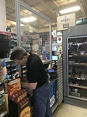 Ed Hyatt, with Metrol Exhibit Corporation in Romeoville, installs a Plexiglass Protective Barrier at Joe's Beverage Warehouse in Joliet.
