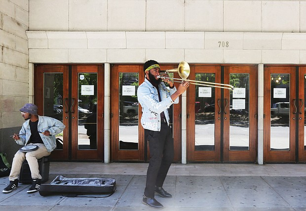 """Isaiah """"Prince Trombone"""" Robinson serenades passing motorists as fellow musician, Robert Johnson III, accompanies him on an electric drum outside The National in the 700 block of East Broad Street. The venue currently is closed because of the coronavirus. The two 23- year-old musicians began their impromptu concerts after they were laid off from their full-time gigs. Their goal: To deliver some upbeat sounds to counter the pandemic's gloom and to possibly earn some spare change from the few pedestrians in Downtown. Other in Richmond musicians have been sharing their talents on their porches or in parks. One example is saxophonist James """"Plunky"""" Branch, who regularly turns his porch into a solo concert platform for those within earshot in his West End neighborhood."""