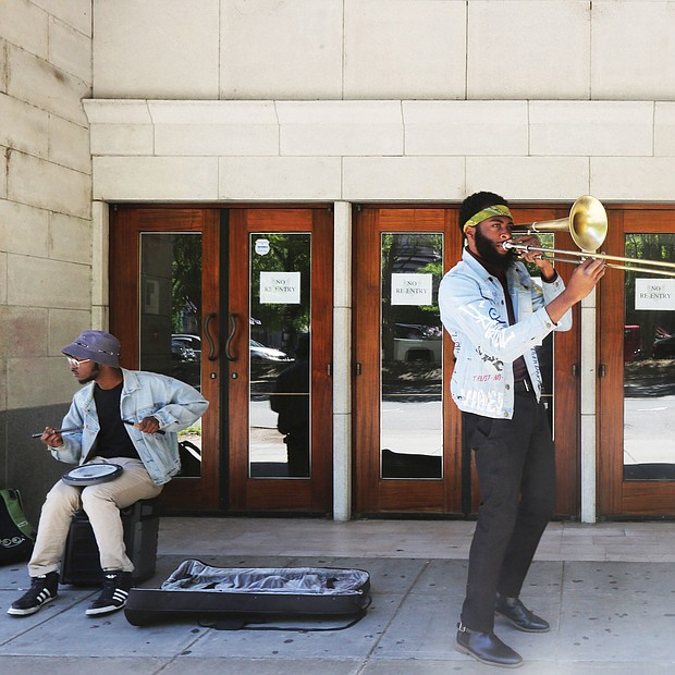 "Isaiah ""Prince Trombone"" Robinson serenades passing motorists as fellow musician, Robert Johnson III, accompanies him on an electric drum outside The National in the 700 block of East Broad Street. The venue currently is closed because of the coronavirus. The two 23- year-old musicians began their impromptu concerts after they were laid off from their full-time gigs. Their goal: To deliver some upbeat sounds to counter the pandemic's gloom and to possibly earn some spare change from the few pedestrians in Downtown. Other in Richmond musicians have been sharing their talents on their porches or in parks. One example is saxophonist James ""Plunky"" Branch, who regularly turns his porch into a solo concert platform for those within earshot in his West End neighborhood."