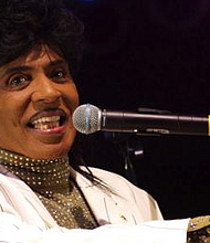 Little Richard performing at the University of Texas Forty Acres Festival in 2007. Little Richard's high-energy performances while playing the piano included dancing on top of the piano, running on and off the stage and throwing souvenirs to the audience. He also dressed flamboyantly onstage. Some of what is taken for granted now in popular music was invented by Little Richard. (Photo: Little Richard performing at the University of Texas Forty Acres Festival in 2007.