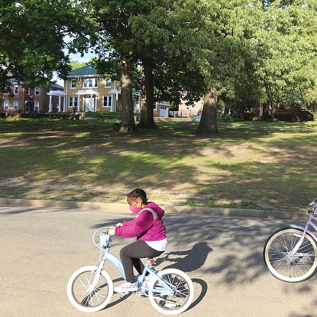 Malea Claud, 7, and her mother, Melissa Claud, regularly finish their day with a leisurely bike ride around Byrd Park. Here, they are riding Tuesday near Swan Lake. Ms. Claud reminded her daughter to secure her mask before they took off in the evening breeze.
