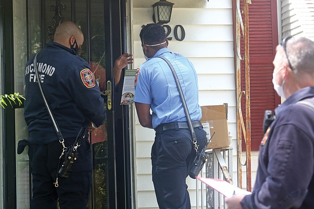 City firefighters Walter Davis, left, and Kevin Henderson, center, and fire Lt. Mark Chase deliver face masks, hand sanitizer and information to a resident on North 20th Street in Church Hill on Tuesday. The team from Fire Station 11 was taking part in the city's effort to distribute thousands of protective items to people in the areas regarded as high risk for COVID-19.