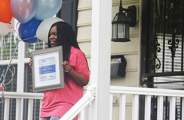 Rahmah T. Johnson proudly displays the plaque naming her Richmond's Teacher of the Year last Friday. A counselor at Thomas Jefferson High School, Ms. Johnson found out about her selection when a delegation including Richmond Schools Superintendent Jason Kamras, Mayor Levar M. Stoney and other officials surprised her at her North Side home.