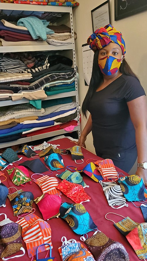 Jillian Soluade stands by face masks sewn by her husband, Abiodun Soluade. She is wearing one of their company's stylist creations. Jillian has been actively encouraging others to wear face masks, through her social media presence.