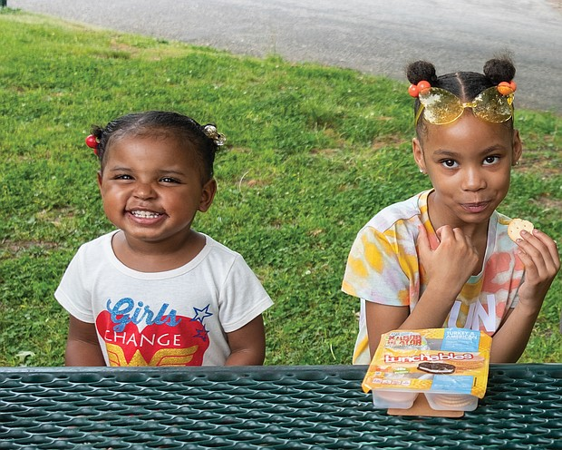 Harmony Johnson, 3, left, and her cousin, 6-year-old London Johnson, have lunch last Friday in Forest Hill Park on South Side. They were enjoying the park and warm temperatures with London's mom, Kristina Johnson. After scattered thunderstorms on Friday and Saturday, the Memorial Day weekend is expected to be sunny, with high temperatures in the mid to low 70s.