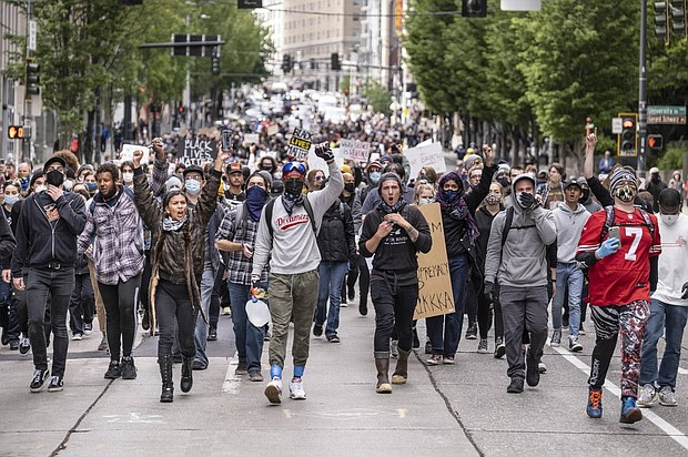 Protestors in Seattle march on Sunday, May 31to call for justice over the death of George Floyd, a black man who died May 25 after being restrained by Minneapolis police officers. (Ken Lambert/The Seattle Times via AP)