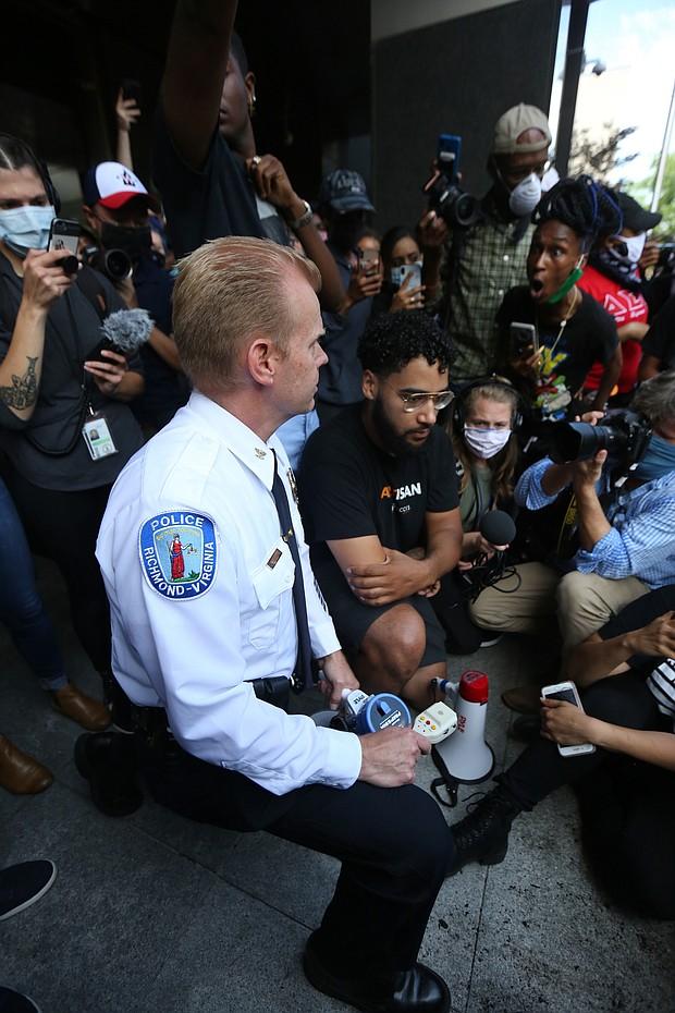 Police Chief Will smith takes a knee at a joint press conference with Mayor Levar M. stoney on Tuesday outside City Hall where they apologized to the crowd for police using tear gas and pepper spray on a peaceful crowd on Monday night at the Lee statue.