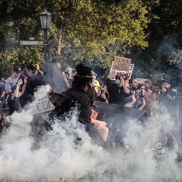 Protesters participating in a peaceful demonstration react to being hit by Richmond Police with tear gas and pepper spray on Monument Avenue at the Robert E. Lee statue on Monday about 30 minutes before the city's curfew.