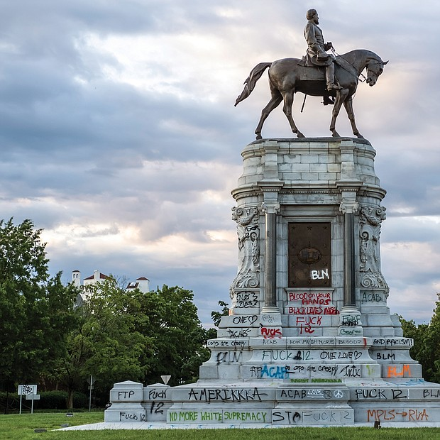 Daylight reveals the spray-painted pedestal of the Robert E. Lee statue at Monument and Allen avenues.