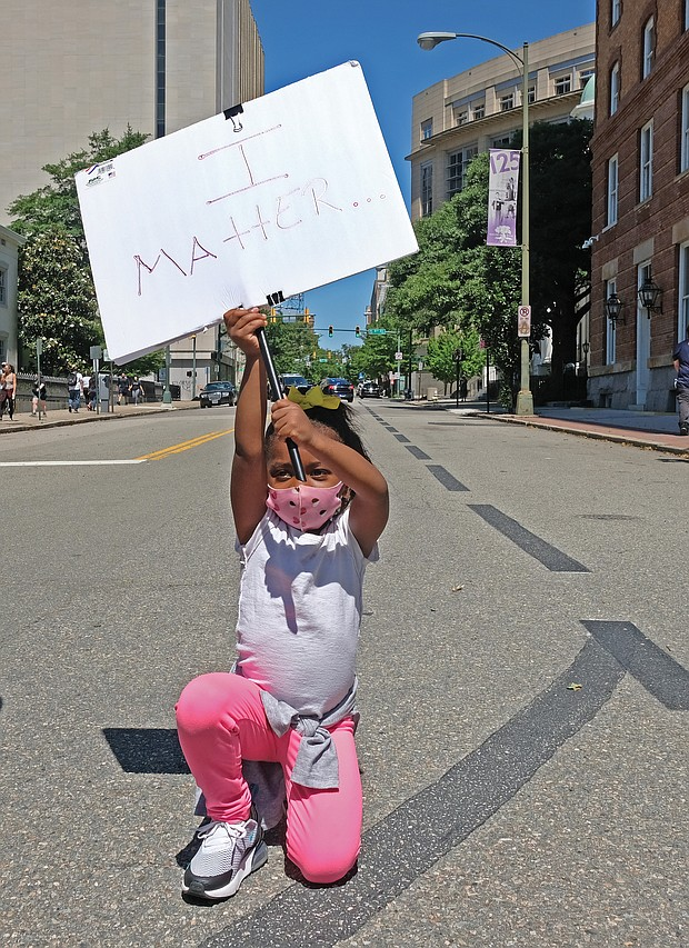 Nasiah Morris, 4, carries a sign with a powerful message during sunday's peaceful grassroots march from Brown's Island to the 17th street Market in shockoe Bottom. The youngster, kneeling at 9th and Grace streets across from the Capitol, attended the rally with her mother, Toya Morris, and 15-year-old brother, Tye.