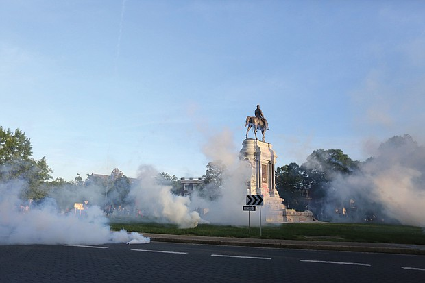 Tear gas clouds the air around the Monument Avenue statue of Confederate Gen. Robert E. Lee on Monday evening when Richmond Police scattered hundreds of peaceful protesters by releasing tear gas and shooting pepper spray about 30 minutes before the 8 p.m. curfew was to go into effect. The Confederate statues are headed for removal under plans announced Wednesday.