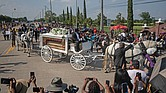 The coffin of George Floyd proceeds to his final resting place next to his mother inside Houston Memorial Gardens in Pearland, Texas, on Tuesday as throngs capture the picturesque farewell on their phones.