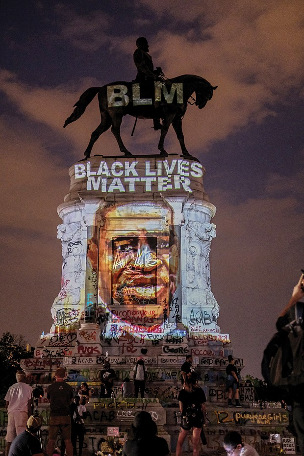 A Black Lives Matter tribute to the late George Floyd is projected onto the statue of Confederate Gen. Robert E. Lee on Saturday night by local artist Dustin Klein, a striking signal of change.